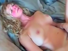 Curly-haired blonde is lying naked on the bed