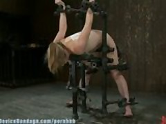 Adrianna Nicole, legs spread wide in metal bondage, helpless and drooling