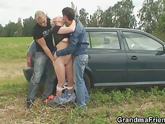 Mature lady in the outdoor threesome